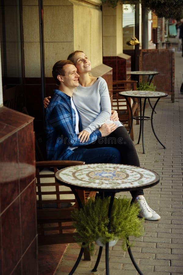 Gelukkige paarzitting in openlucht in een koffie, het meisje in de wapens van de kerel Het glimlachen royalty-vrije stock afbeelding