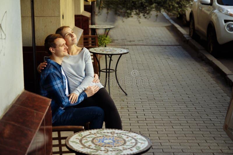 Gelukkige paarzitting in openlucht in een koffie, het meisje in de wapens van de kerel Het glimlachen stock foto