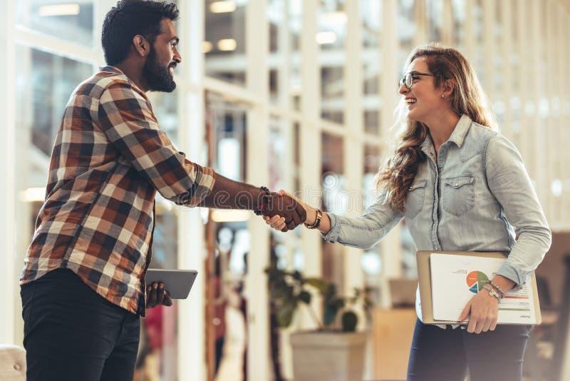 Gelukkige partners die elkaar begroeten op een vergadering stock foto