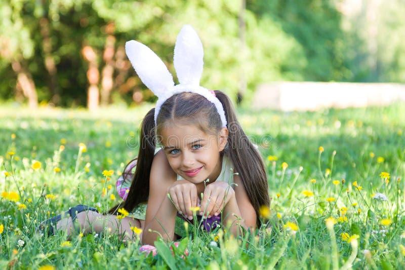 Gelukkige Pasen: aanbiddelijk meisje die konijntjesoren dragen die op het gras in openlucht liggen stock afbeeldingen
