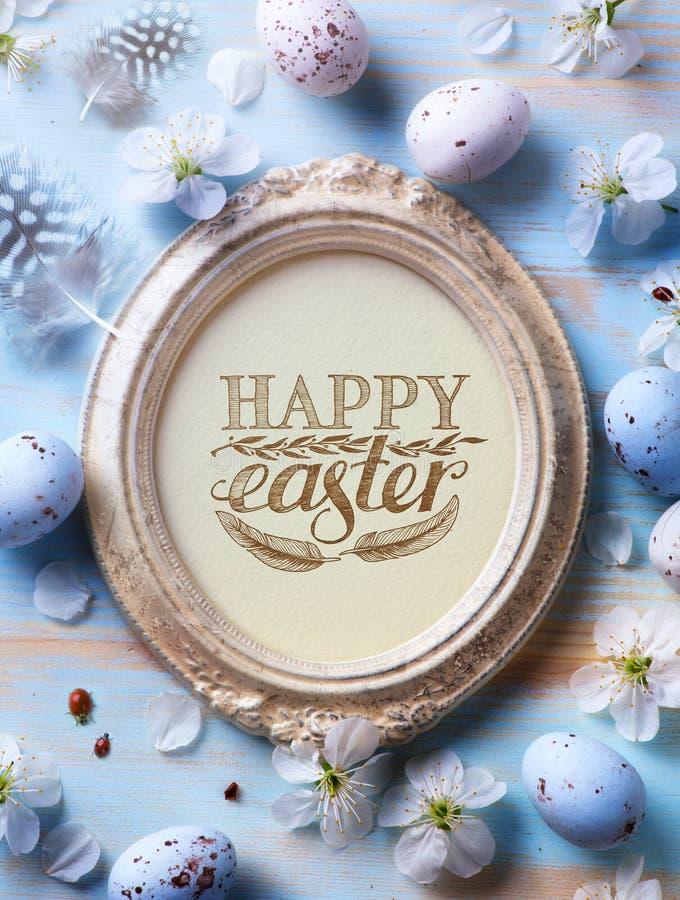 Gelukkige Pasen-Achtergrond; Paasei en de lentebloemen op blauw t