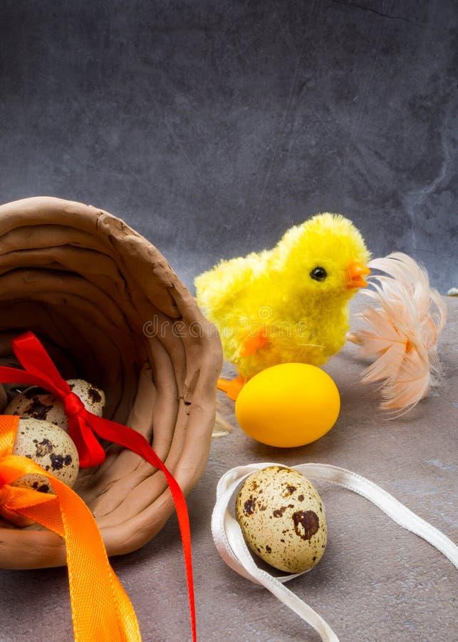 Gelukkige Pasen achtergrond Paaseieren en gele kuiken en kleikom Eieren en kip als Pasen-symbool De groeten van Pasen De lente stock afbeeldingen