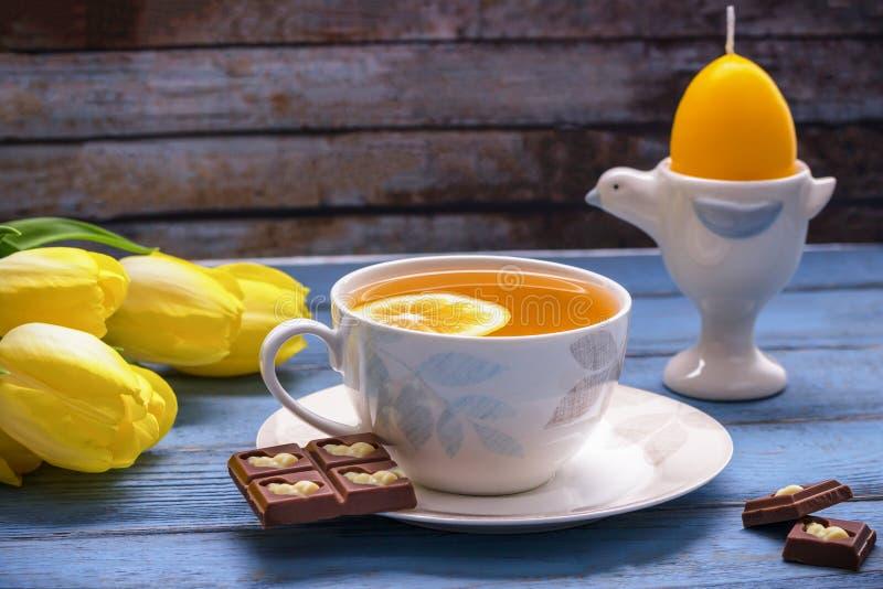 Gelukkige Pasen Citroenthee, melkchocola met Pasen-konijntje, gele tulpen, de gele kaars van Pasen in eivorm op uitstekende achte royalty-vrije stock fotografie