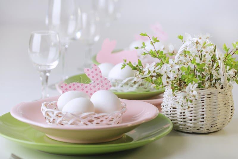 Gelukkige Pasen Decor en lijst het plaatsen van de Pasen-lijst is een vaas met roze tulpen en schotels van roze en groene kleur stock afbeelding