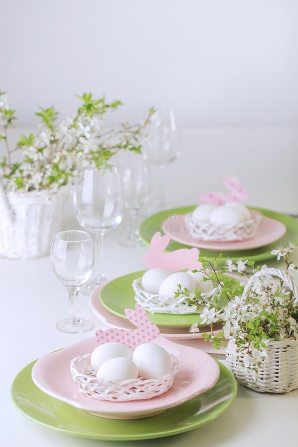 Gelukkige Pasen Decor en lijst het plaatsen van de Pasen-lijst is een vaas met roze tulpen en schotels van roze en groene kleur stock foto