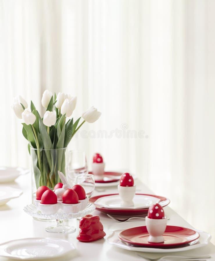 Gelukkige Pasen Decor en lijst het plaatsen van de Pasen-lijst is een vaas met witte tulpen en schotels van rode en witte kleur P stock foto's