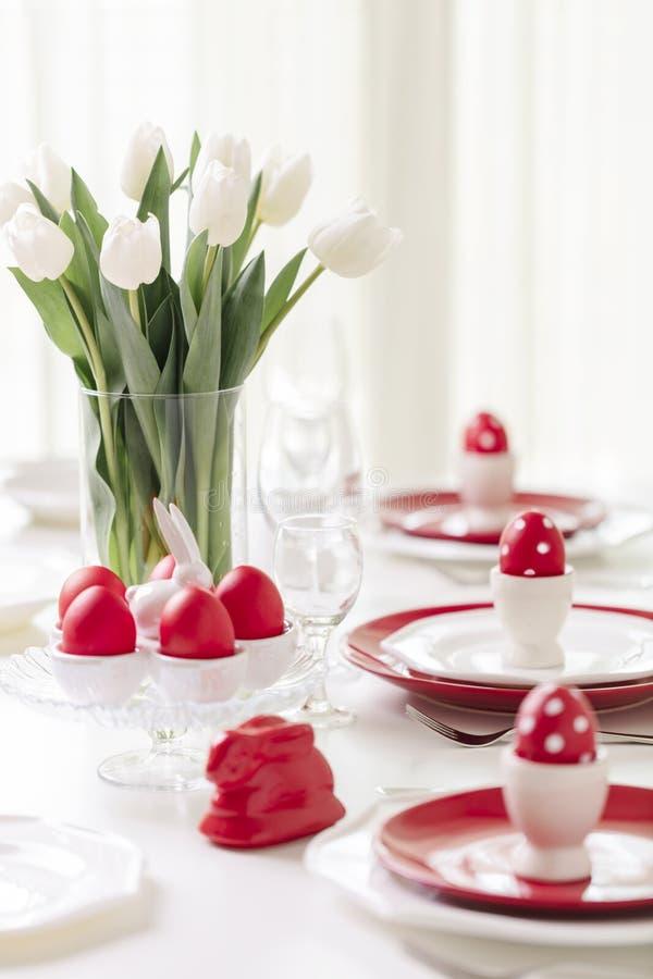 Gelukkige Pasen Decor en lijst het plaatsen van de Pasen-lijst is een vaas met witte tulpen en schotels van rode en witte kleur P stock foto