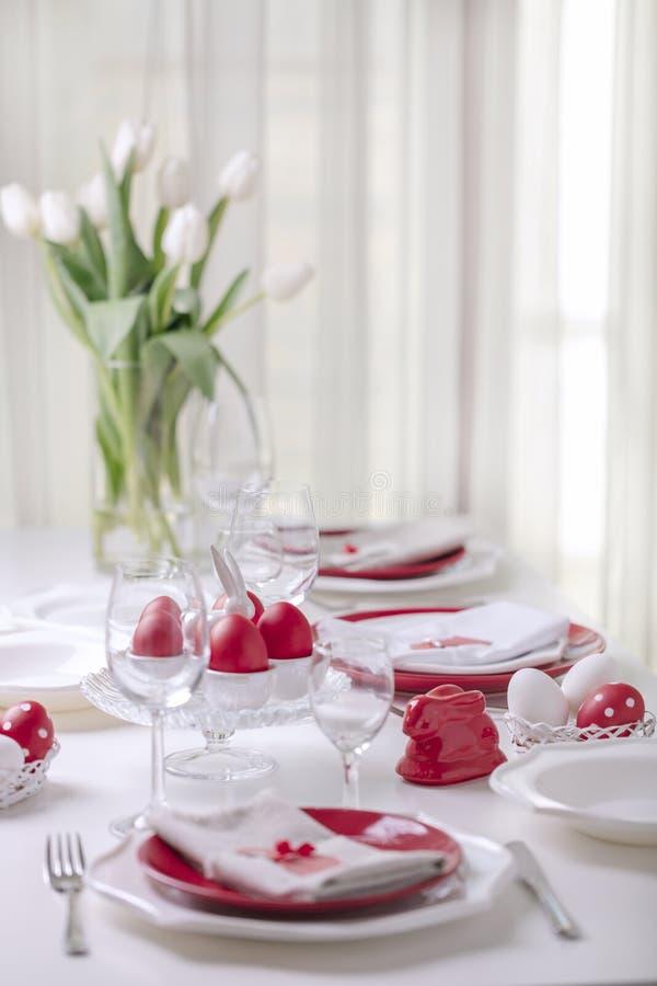 Gelukkige Pasen Decor en lijst het plaatsen van de Pasen-lijst is een vaas met witte tulpen en schotels van rode en witte kleur P royalty-vrije stock afbeelding