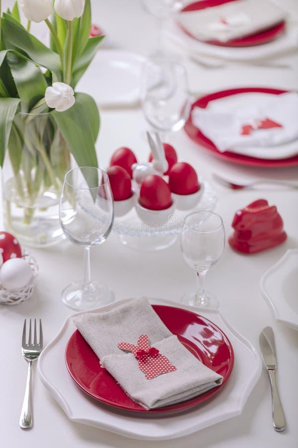 Gelukkige Pasen Decor en lijst het plaatsen van de Pasen-lijst is een vaas met witte tulpen en schotels van rode en witte kleur P royalty-vrije stock fotografie