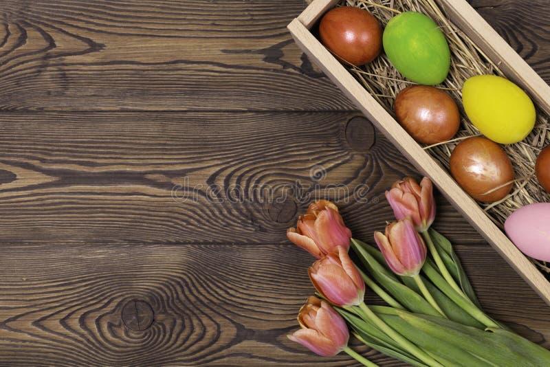 Gelukkige Pasen Felicitatiepasen-achtergrond Paaseieren en Bloemen stock afbeelding