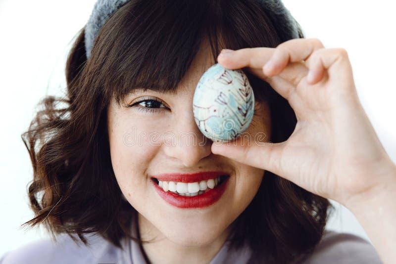 Gelukkige Pasen-groeten Mooie jonge vrouw in konijntjesoren die en paasei glimlachen houden dichtbij gezicht op witte achtergrond stock foto's