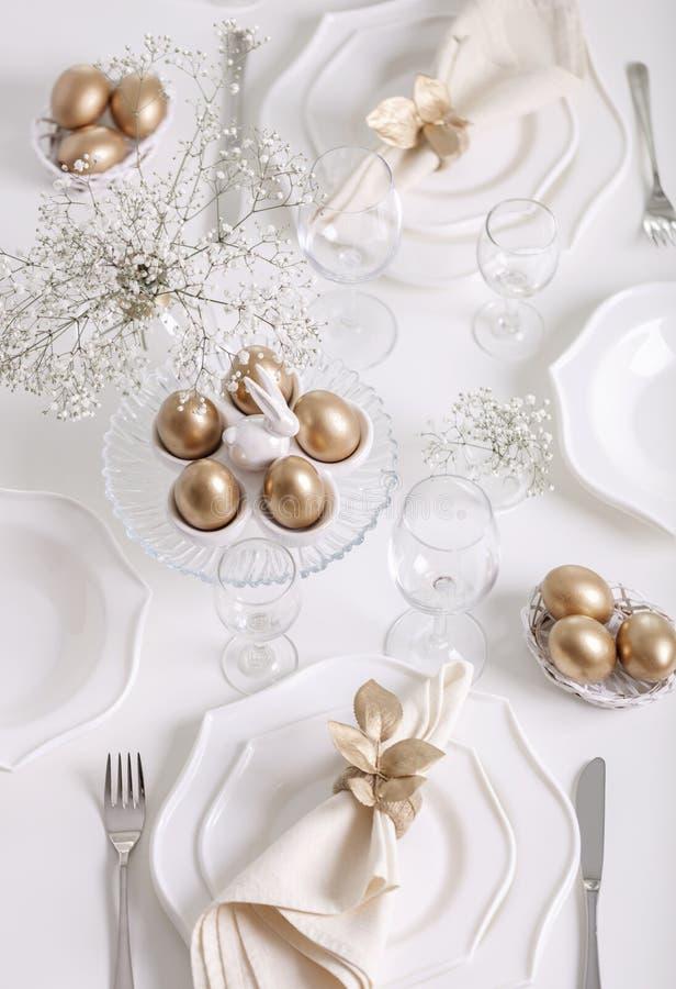 Gelukkige Pasen! Het gouden decor en lijst plaatsen van de Pasen-lijst met witte schotels van witte kleur royalty-vrije stock afbeelding