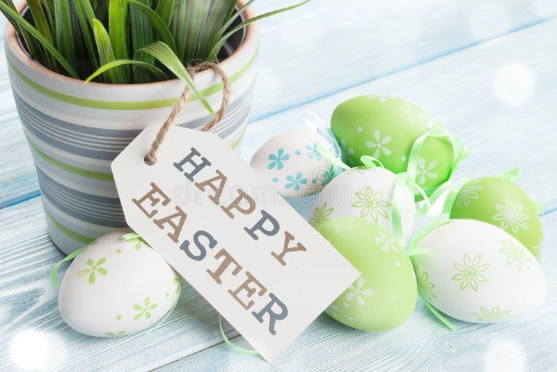 Gelukkige Pasen-tekst geen editable groene en witte gekleurde paaseieren op de blauwe houten achtergrond stock afbeelding