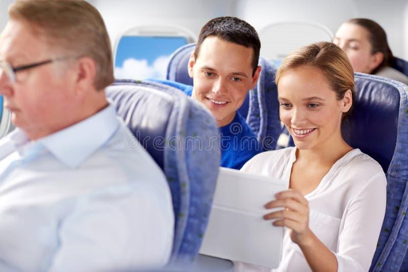 Gelukkige passagiers met koffie die in vliegtuig spreken stock foto
