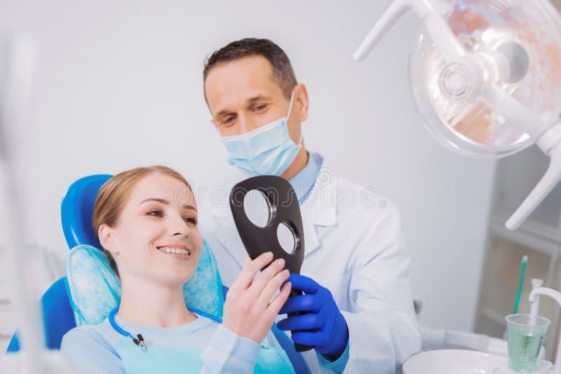 Gelukkige patiënt die in de spiegel na het krijgen van nieuwe steunen kijken royalty-vrije stock afbeelding