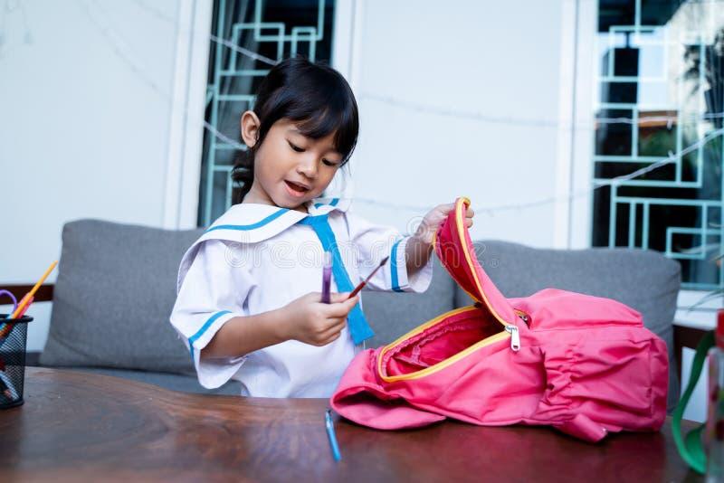 Gelukkige peuter met eenvormige school voorbereidend haar zelf voor school royalty-vrije stock afbeeldingen
