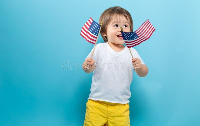 Gelukkige peuterjongen die Amerikaanse vlaggen golven royalty-vrije stock foto