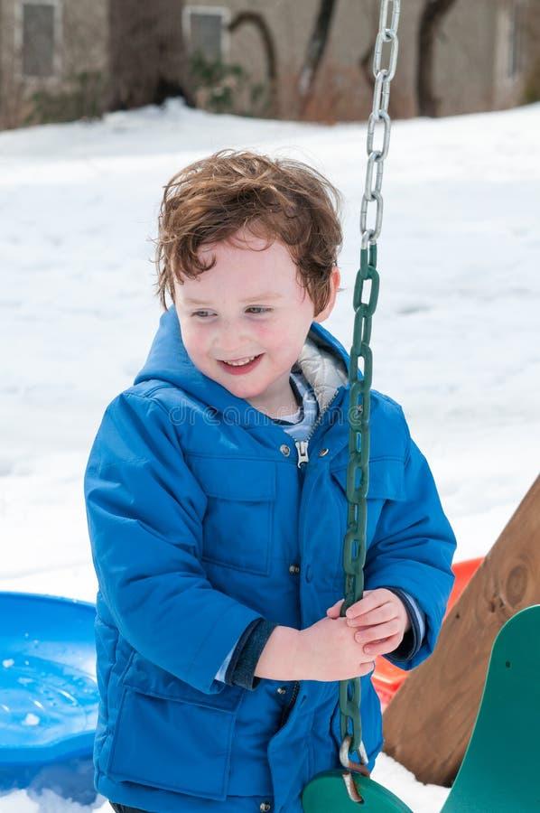 Gelukkige peuterjongen in warme laag op sneeuwdag en het hebben van een pret in de winter buiten, openluchtportret stock afbeelding