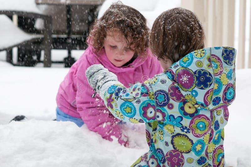Gelukkige peutersibling meisjes in warme laag en gebreide hoed die omhoog sneeuw werpen en een pret in de winter hebben buiten, o stock afbeelding