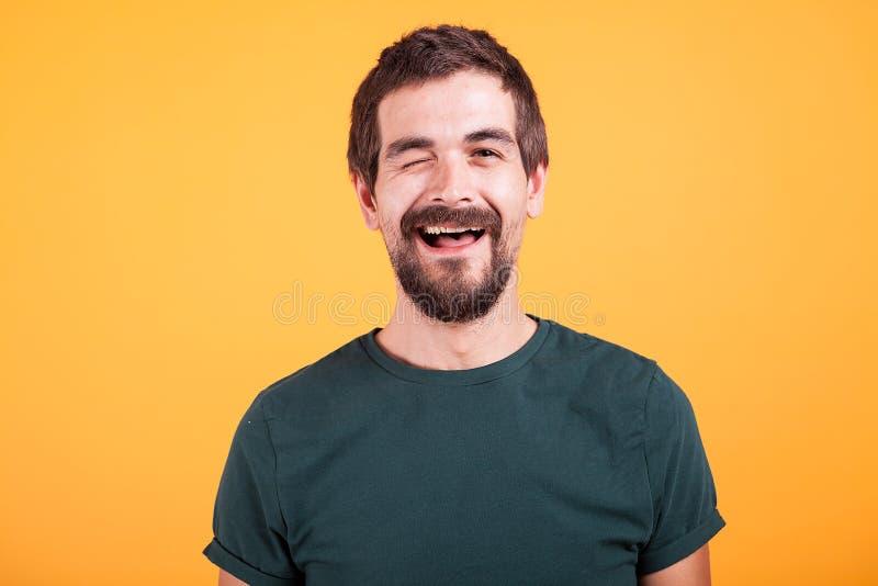 Gelukkige positieve mens die de camera en het knipogen bekijken royalty-vrije stock foto