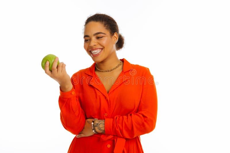 Gelukkige positieve vrouw die de appel bekijken stock fotografie