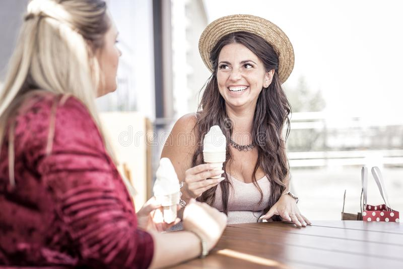 Gelukkige positieve vrouwen die smakelijk roomijs proberen stock afbeeldingen