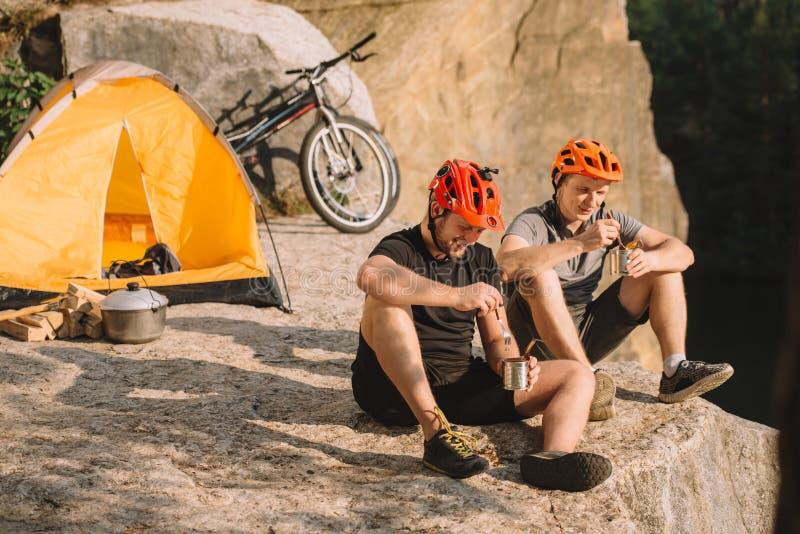 gelukkige proeffietsers die ingeblikt voedsel in het kamperen eten royalty-vrije stock afbeelding