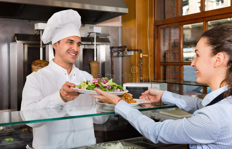 Gelukkige professionele chef-kok en jonge serveerster die kebab nemen royalty-vrije stock afbeeldingen