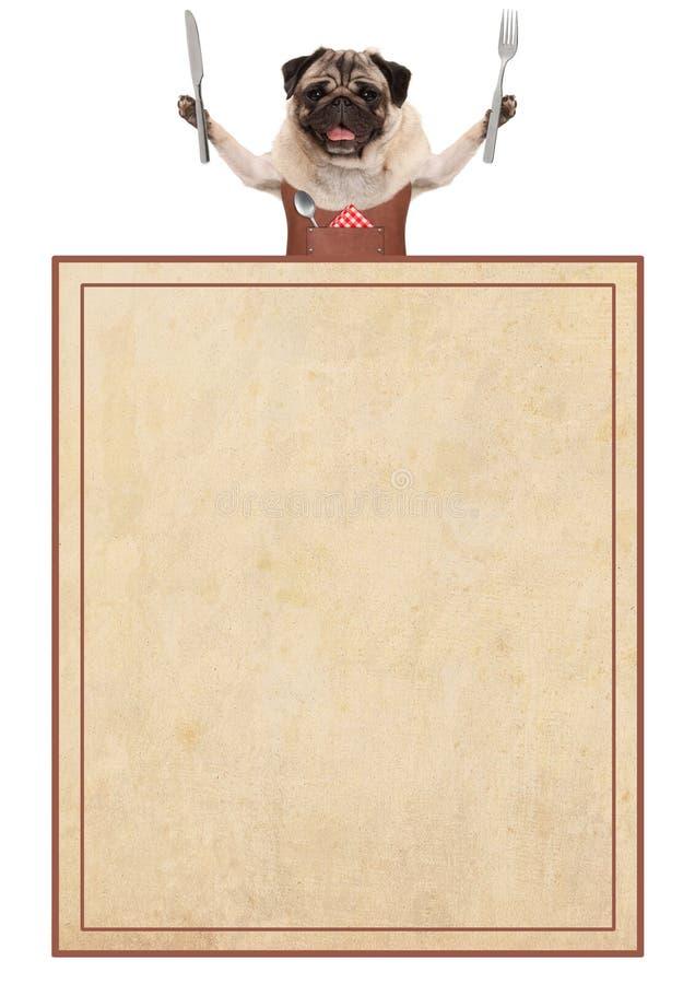 Gelukkige pug hond die leerbbq schort dragen, die bestek voor het eten, met oude uitstekende document menukaart houden stock foto's