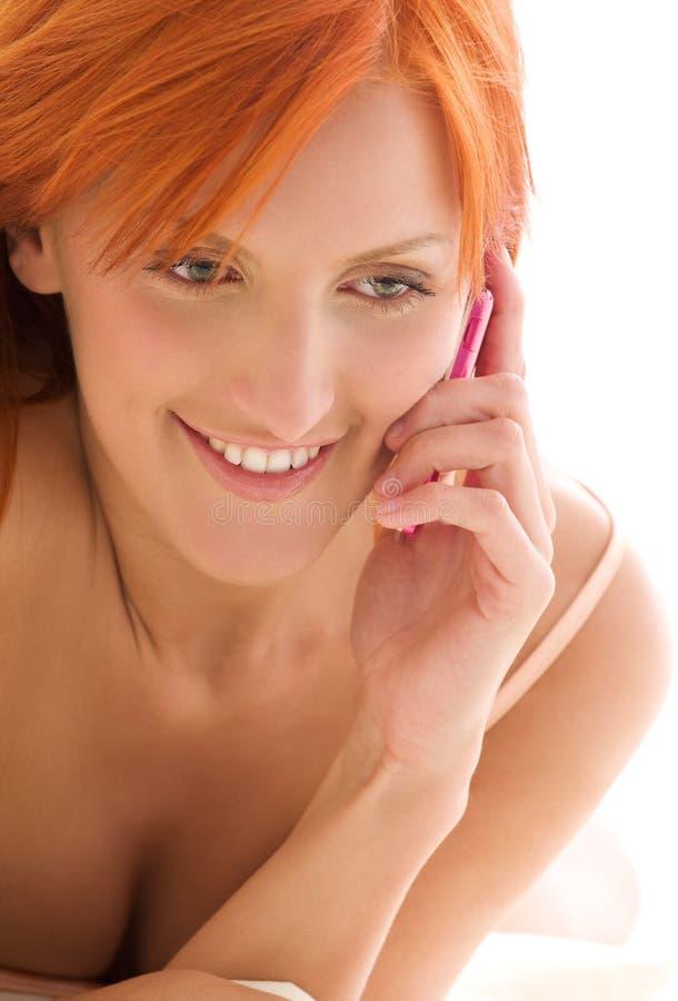 Gelukkige redhead vrouw met celtelefoon stock fotografie