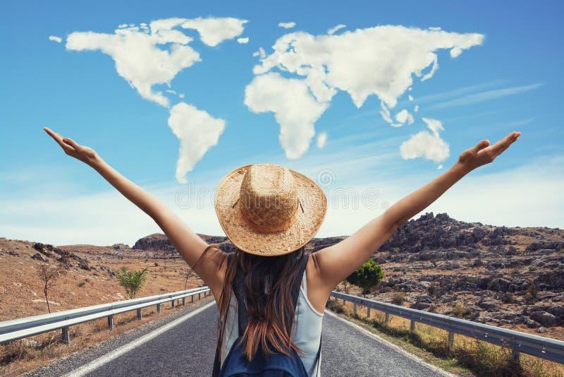 Gelukkige reisvrouw op vakantieconcept met wereld gevormde wolken De grappige reiziger geniet van haar reis en klaar aan avontuur royalty-vrije stock afbeelding