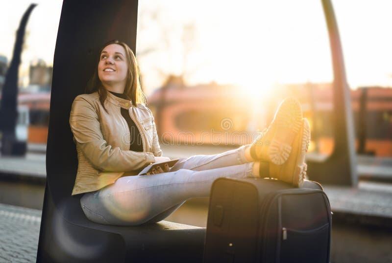Gelukkige reiziger die benen en schoenen op koffer houden stock afbeeldingen