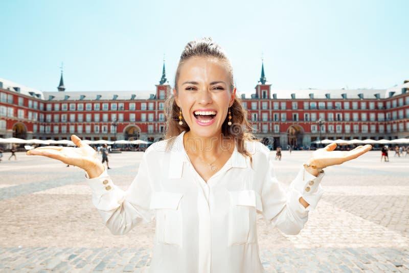 Gelukkige reizigersvrouw die iets op lege palm voorstellen royalty-vrije stock foto's