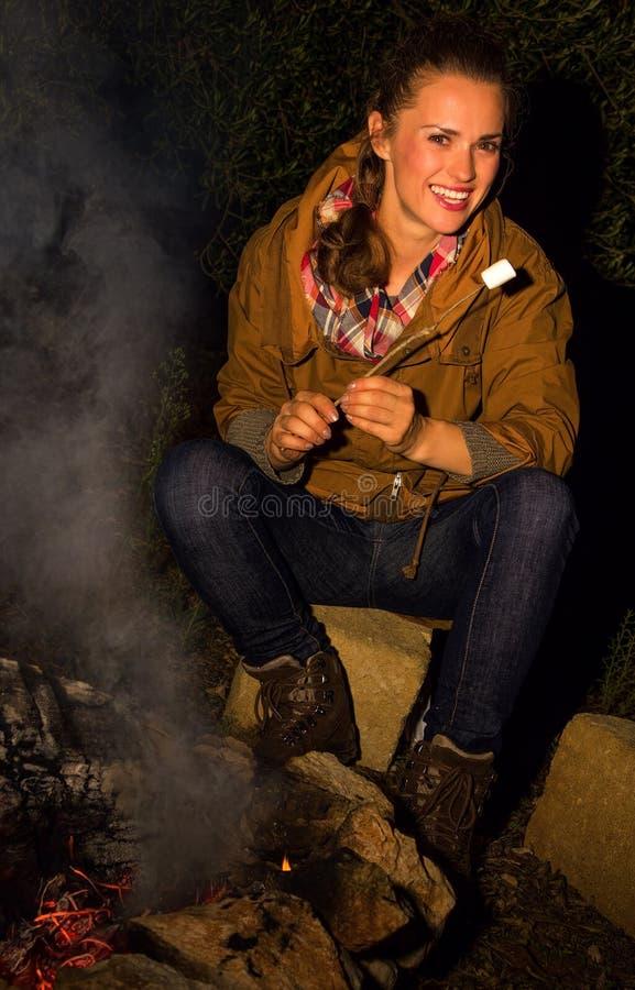 Gelukkige reizigersvrouw door het kamperen brand met geroosterde heemst stock foto's