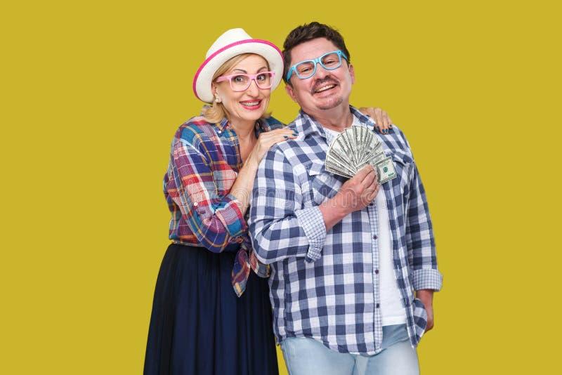 Gelukkige rijke familie, volwassen man en vrouw in toevallig geruit overhemd die pickaback, houdend toothy ventilator van dollar, stock fotografie