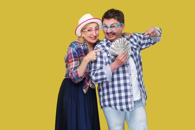 Gelukkige rijke familie, volwassen man en vrouw in toevallig geruit overhemd die pickaback, houdend ventilator van dollar zich ve royalty-vrije stock foto