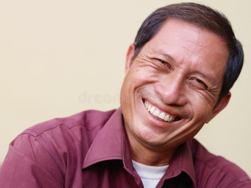 Gelukkige rijpe Aziatische mens die bij camera glimlacht stock fotografie