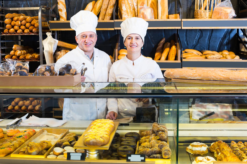 Gelukkige rijpe bakkers met vers brood in bakkerij royalty-vrije stock fotografie