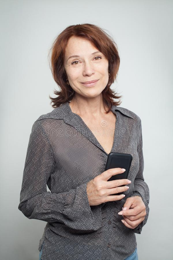 Gelukkige rijpe bedrijfsvrouw met celtelefoon royalty-vrije stock afbeeldingen