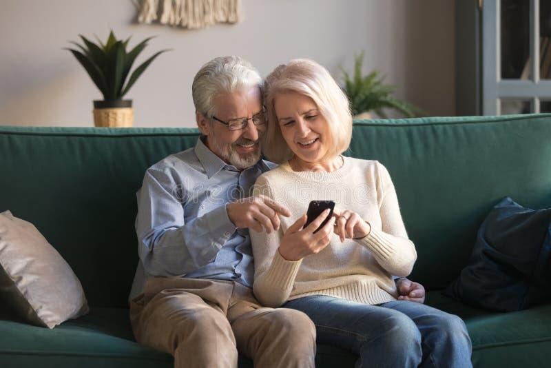 Gelukkige rijpe familie, vrouw en echtgenoot die telefoon samen thuis met behulp van royalty-vrije stock afbeeldingen
