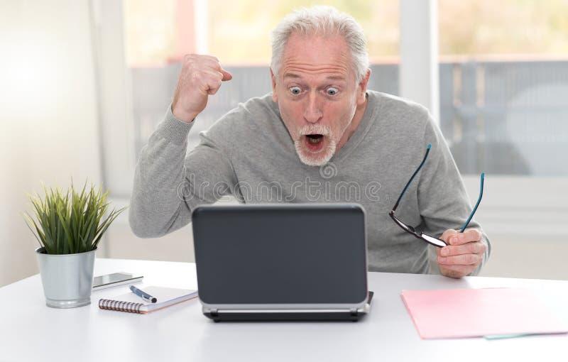 Gelukkige rijpe mens die een goede verrassing op laptop hebben stock fotografie