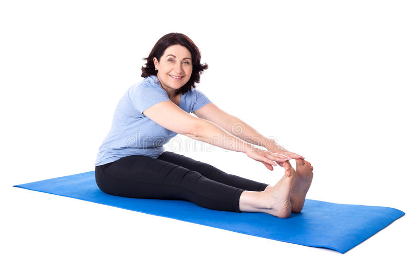 Gelukkige rijpe vrouw die uitrekkende oefeningen op yogamat isolat doen stock foto