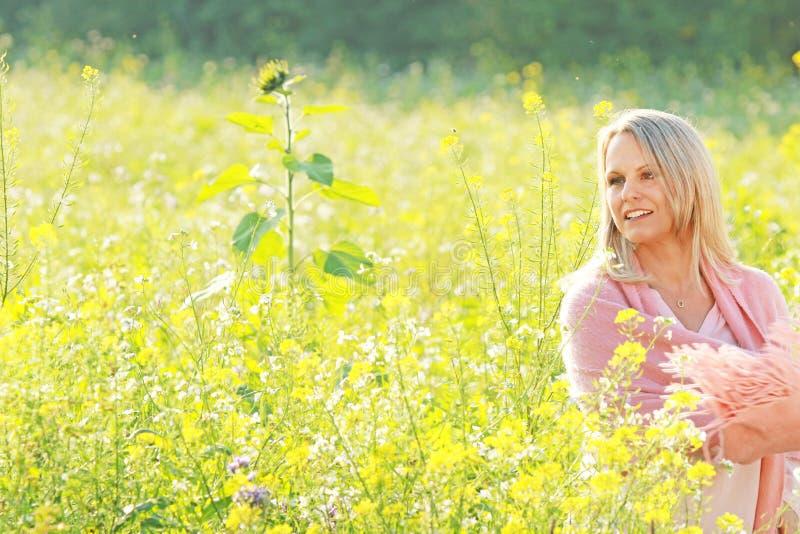 Gelukkige rijpe vrouw in een flowerfield royalty-vrije stock fotografie