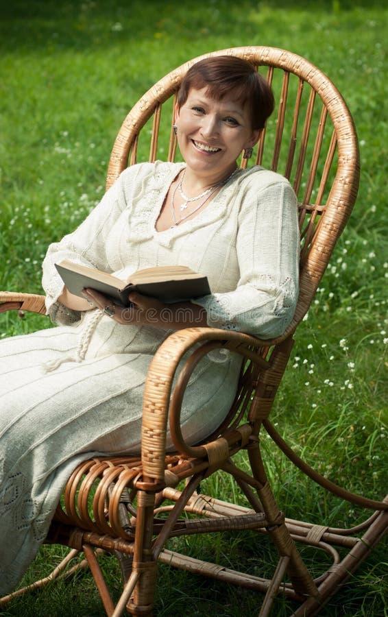 Gelukkige rijpe vrouw met boek in schommelstoel royalty-vrije stock foto