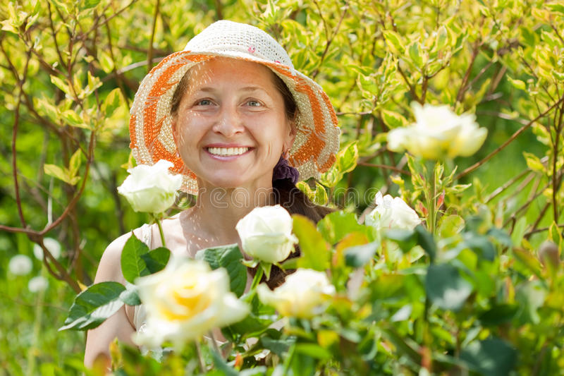 Gelukkige rijpe vrouw in rozeninstallatie stock afbeelding