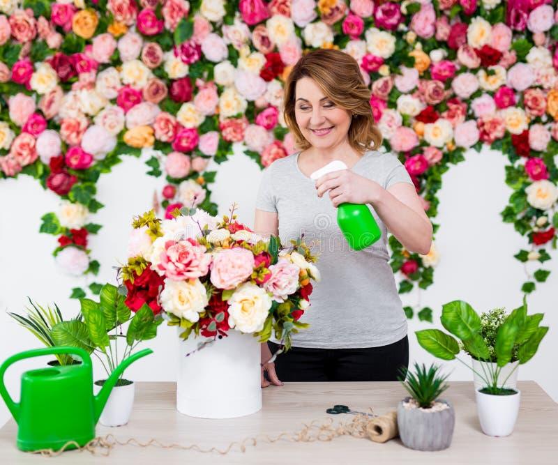 Gelukkige rijpe vrouwelijke bloemist of tuinman die in bloemwinkel werken royalty-vrije stock afbeelding