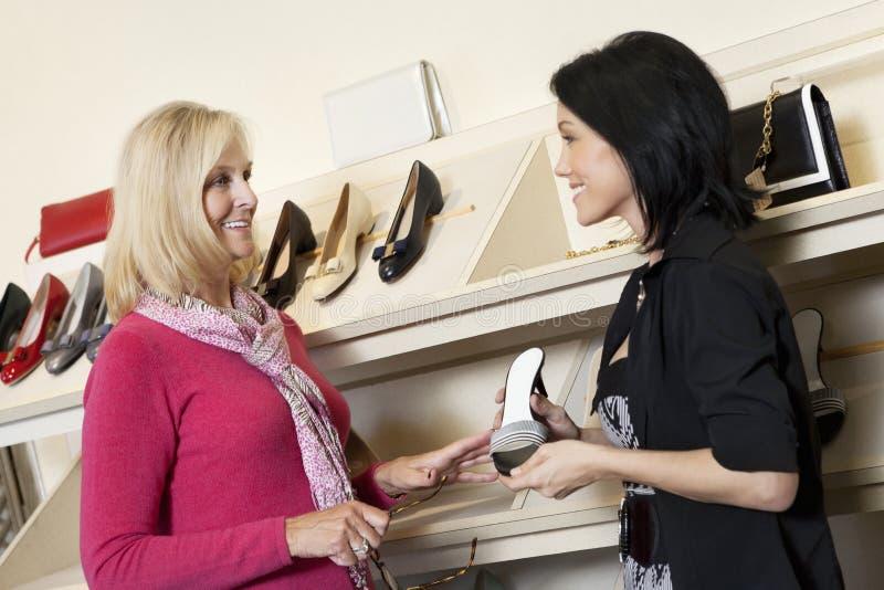 Gelukkige rijpe winkelbediende met medio volwassen klant in schoenopslag stock foto