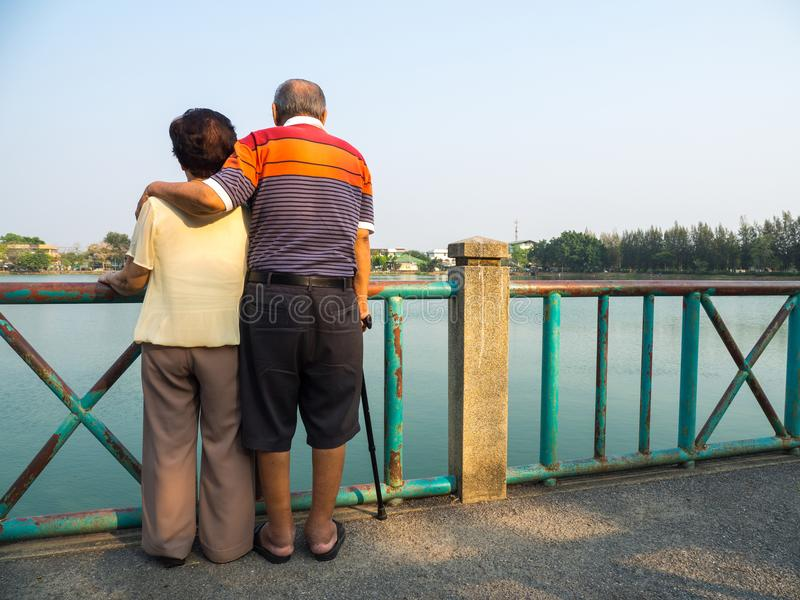 Gelukkige romantische hogere Aziatische paartribune op de brug voor het meer Echtgenoottribunes met zijn vrouw Concept oudste cou stock foto