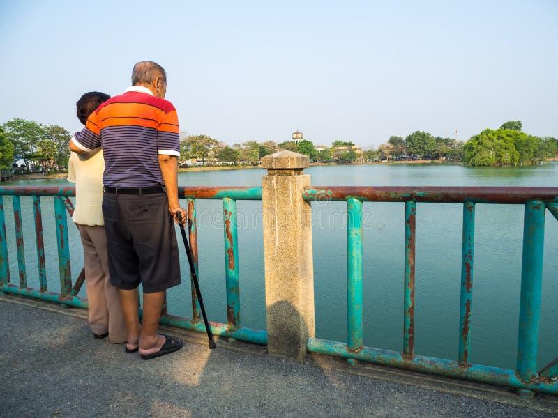 Gelukkige romantische hogere Aziatische paartribune op de brug voor het meer Echtgenoottribunes met zijn vrouw Concept oudste cou stock afbeelding