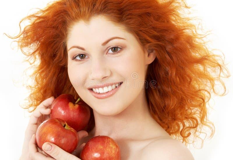 Gelukkige roodharige met rode appelen stock foto